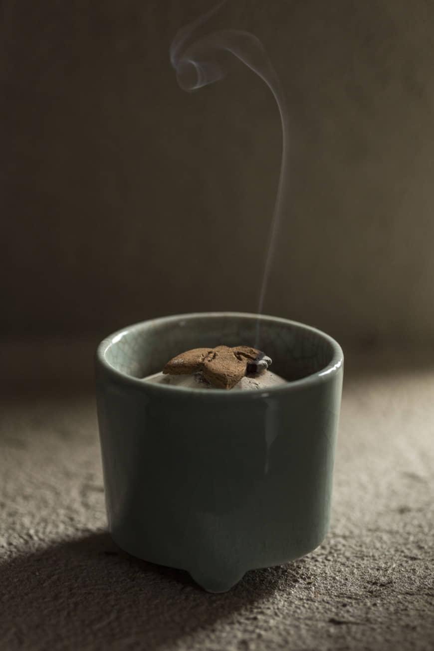 Brûlure lente: Une traînée de fumée parfumée se recourbe à partir d'encens pressé en forme de feuilles de bambou. | RYOICHI OKAZAKI