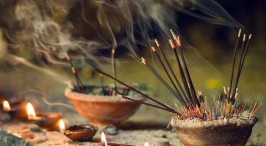 Stick incenses burning in a ceramic bowl