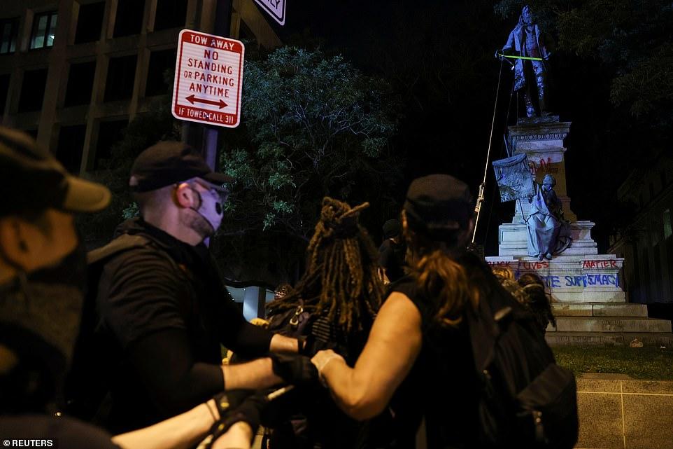 WASHINGTON D.C .: Les manifestants ont enroulé des cordes jaunes autour de la statue et l'ont traînée vers le bas