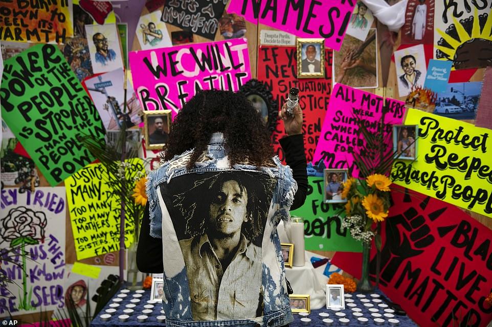 """À Los Angeles, un résident du nom de Jasmine Jackson (photo) a brûlé de l'encens lors d'un changement de prière lors d'une célébration du 19 juin vendredi. L'autel a été décoré dans des affiches de protestation qui disaient: «Nous respirerons! et """"Dites leurs noms!"""""""