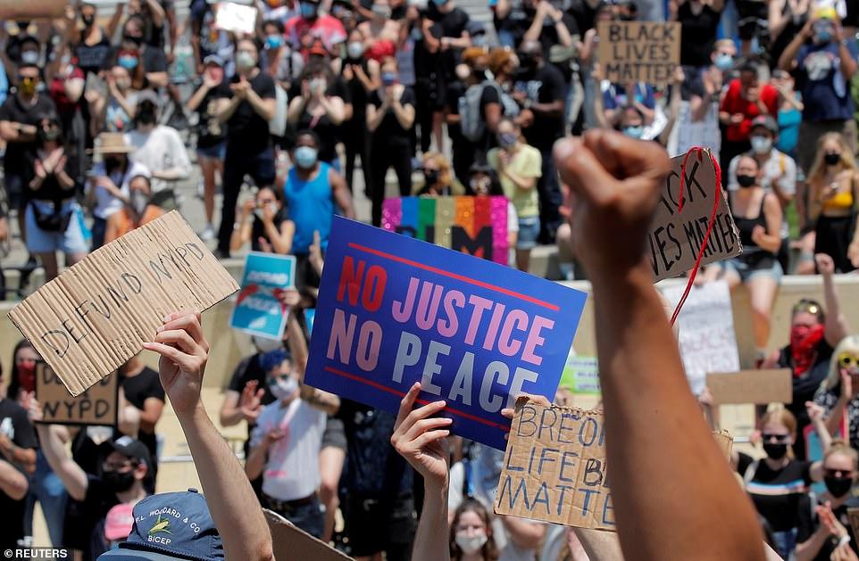 Des manifestants lisant 'Defund NYPD', 'No Justice, No Peace' et 'Black Lives Matter' ont été tenus en l'air vendredi par des manifestants à New York alors qu'ils luttaient contre la brutalité policière