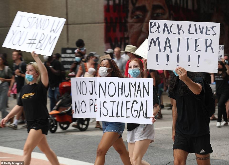 Vendredi, deux femmes tenant des pancartes de protestation dans le centre-ville d'Atlanta, en Géorgie, alors que des dizaines de résidents se rassemblaient