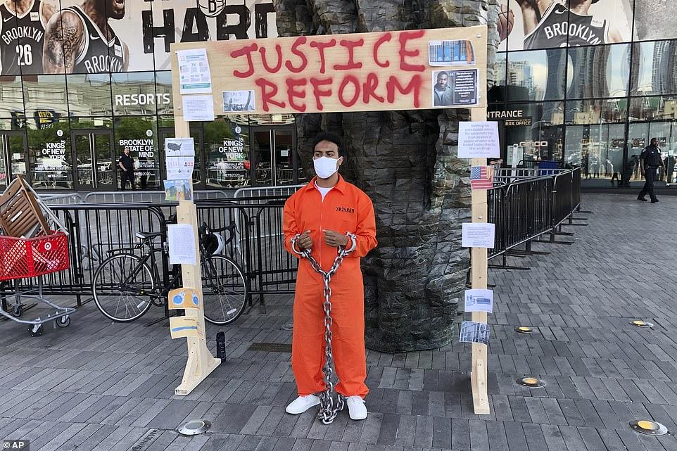 Rama Guzma (photo) portait une combinaison et des chaînes de prison lors d'un rassemblement du 19 juin au Barclay's Center dans le quartier de Brooklyn à New York