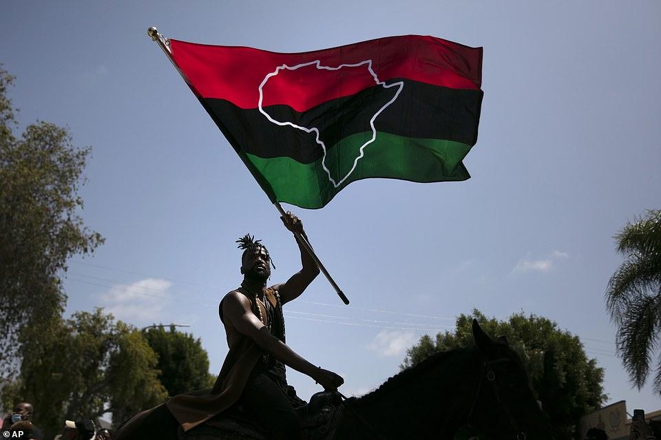 Rein Morton brandit un drapeau panafricain à cheval lors d'une célébration du Juneteenth à Los Angeles vendredi