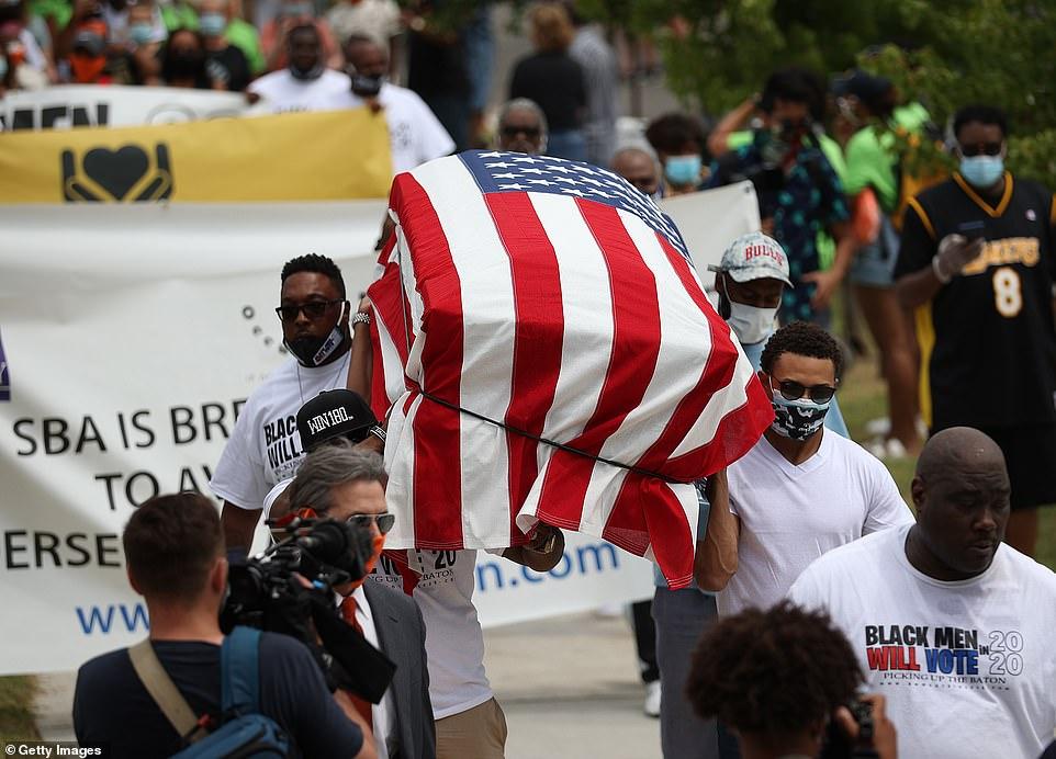 Les gens portent un cercueil symbolique vide drapé d'un drapeau américain lors d'une marche et d'une célébration du 19 juin dans le quartier de Greenwood - la même ville, le président Trump a initialement annoncé un rassemblement électoral avant de déplacer la date sous la pression