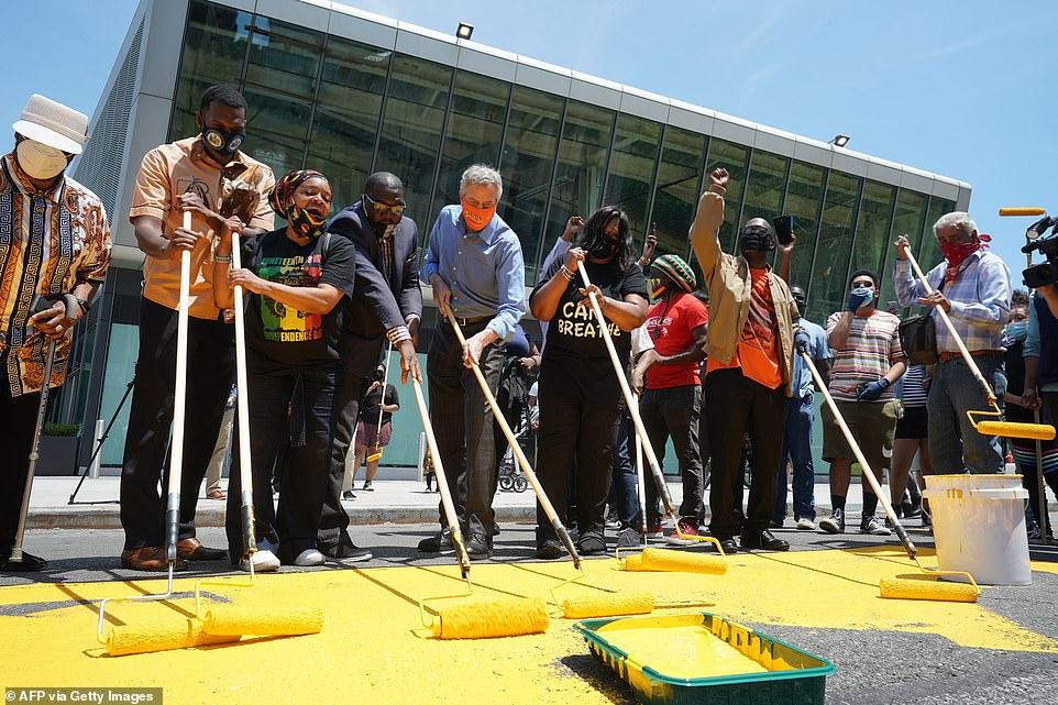 Vendredi, le maire de New York, Bill de Balsio (centre, masque orange), a rejoint un groupe de volontaires de la communauté de Staten Island pour peindre la phrase `` Black Lives Matter '' près du 120e arrondissement. De Blasio a annoncé vendredi que Juneteenth deviendrait un jour férié officiel dans la ville