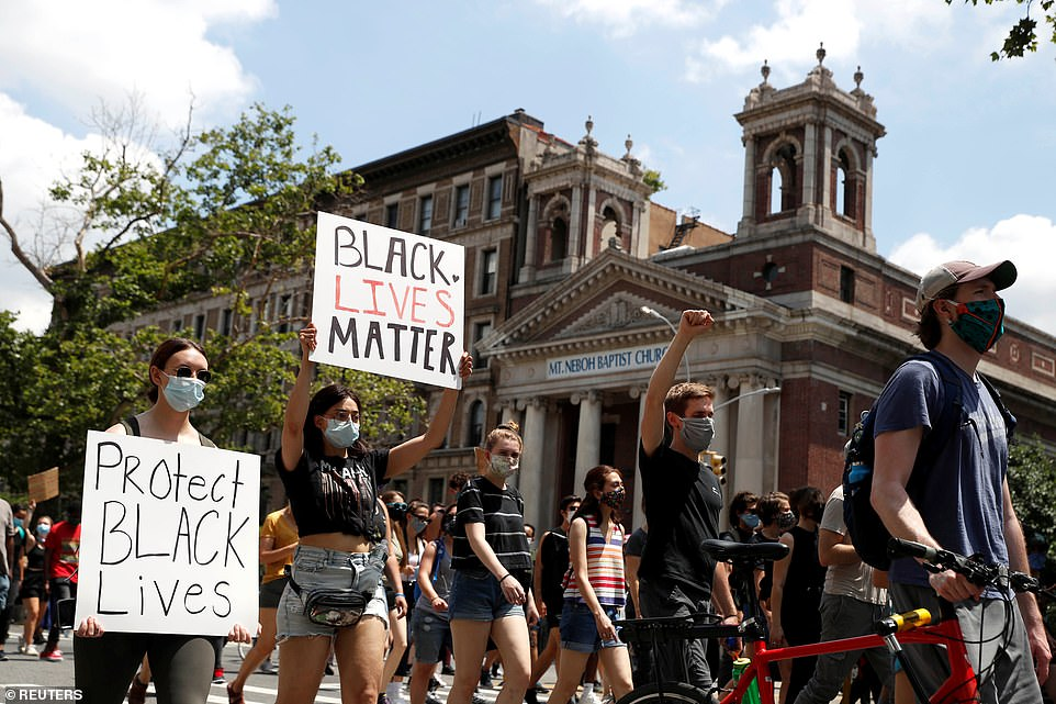 A number of protesters holding 'Black Lives Matter' signs march near the Mt. Neboh Baptist Church in Harlem ahead of an anticipated march on Saturday, which organizers believe will draw several crwods