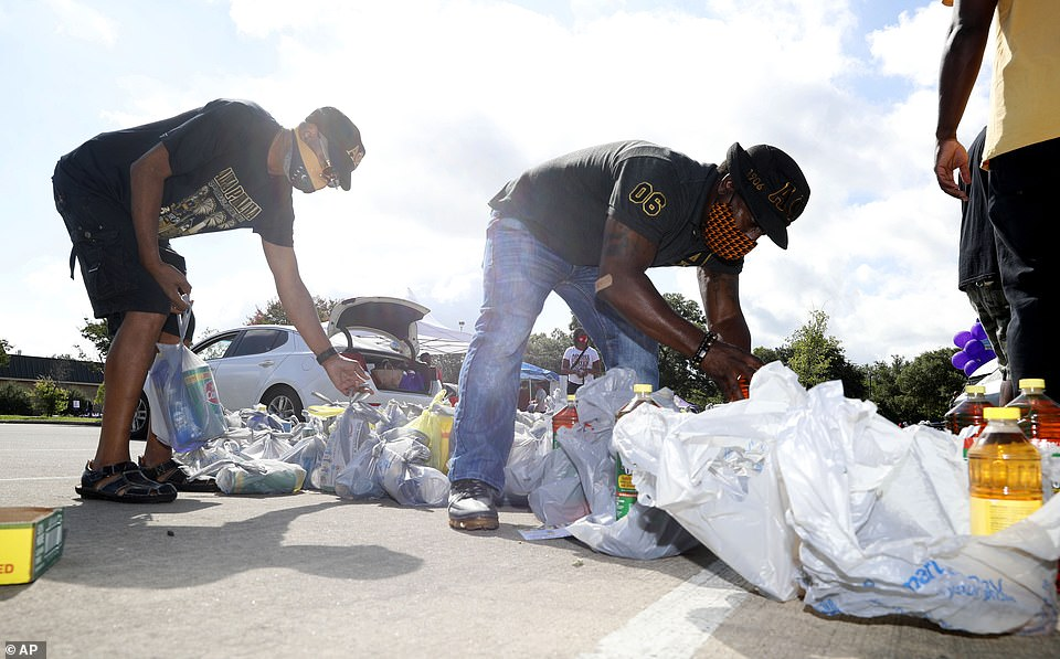 Alpha Phi Alpha fraternity brother Forrest Jackson, right, and Rodrick Tyler prepare bags of cleaning products to distribute during a drive-thru Juneteenth 2020 celebration in Dallas, Texas