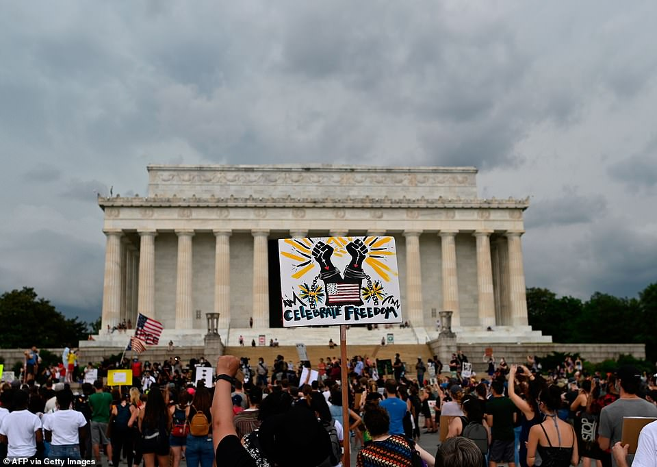 Demonstrators hold signs as they take part in a Juneteenth march and rally in front of the Lincoln Memorial in Washington, DC, (pictured)