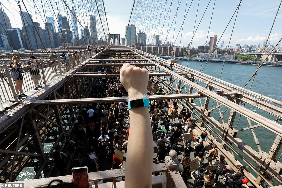 A person raises a fist as people march on the Brooklyn Bridge in New York City on Friday during events to mark Juneteenth