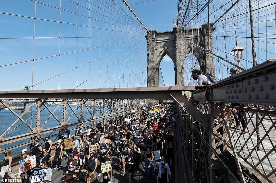 Protesters hold signs that read 'Black Lives Matter' and 'I can't breathe' as they walk across the Brooklyn Bridge on Friday