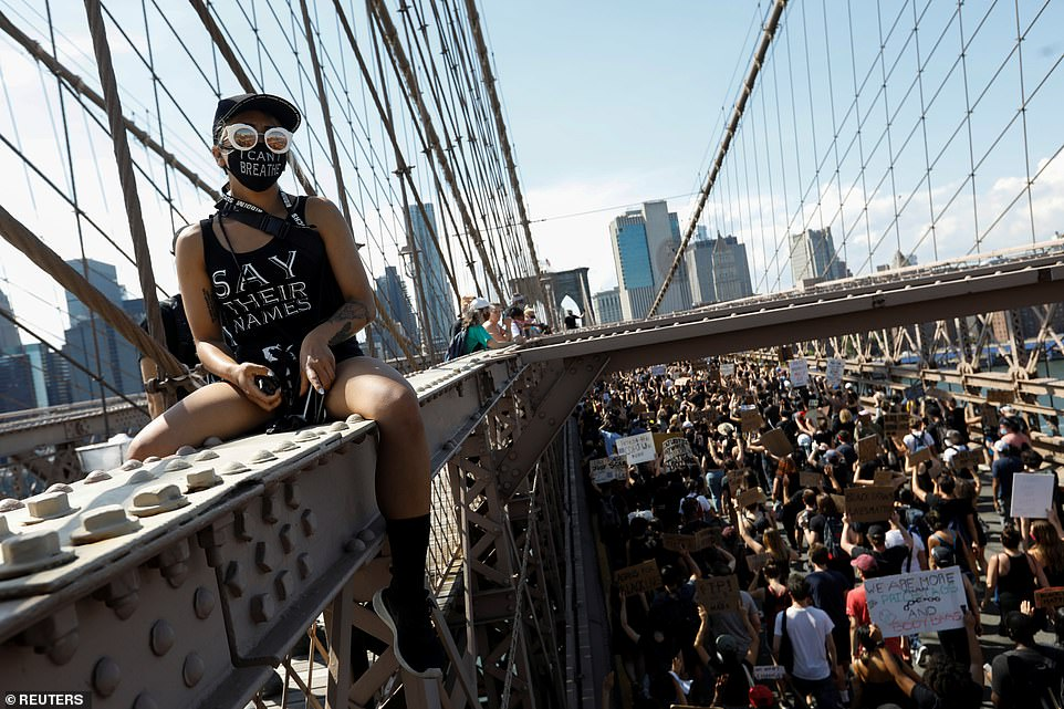 A Black Lives Matter supporter straddles one of the beams lining the Brooklyn Bridge walkway as the protest march goes by on Friday