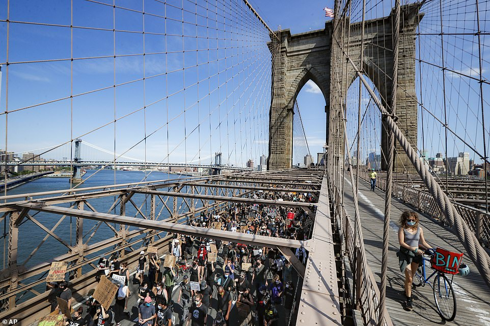 Protesters march over the Brooklyn Bridge towards Manhattan following a Juneteenth rally in Cadman Plaza Park on Friday