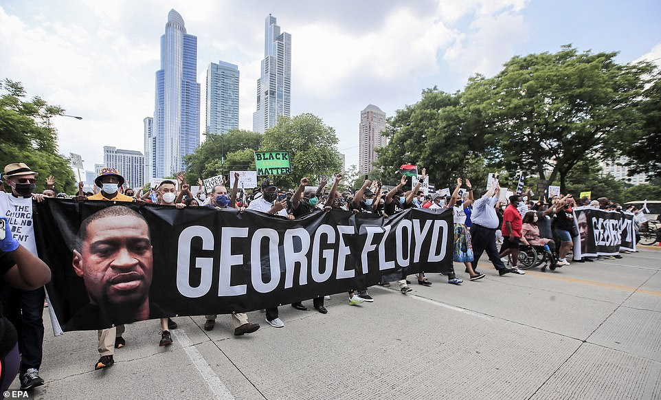 Protesters holds signs remembering George Floyd and chanting slogans during a march in Chicago on Friday
