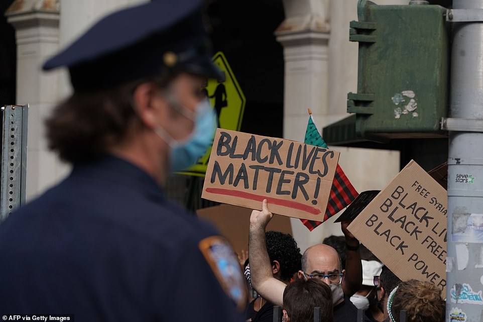 An officer with the New York Police Department looks on as protesters cross the Brooklyn Bridge into Manhattan on Friday