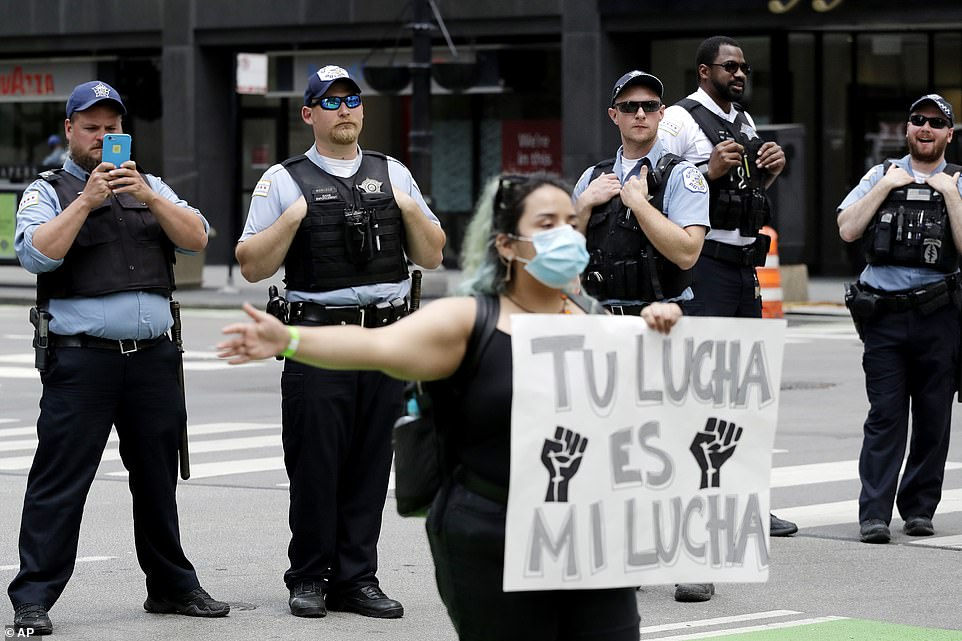 Chicago Police Department officers watch as a protester holds a sign in Spanish that reads 'Your fight is my fight'