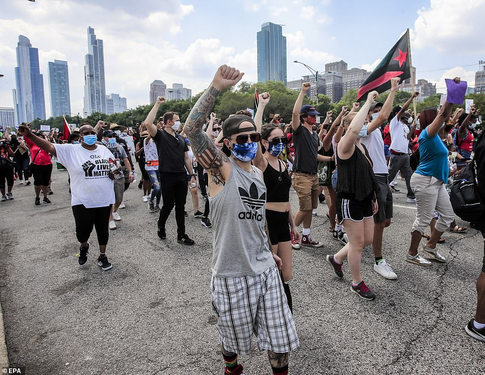 Protesters marching in Chicago on Friday to commemorate Juneteenth raise their fists and chant slogans demanding racial equality