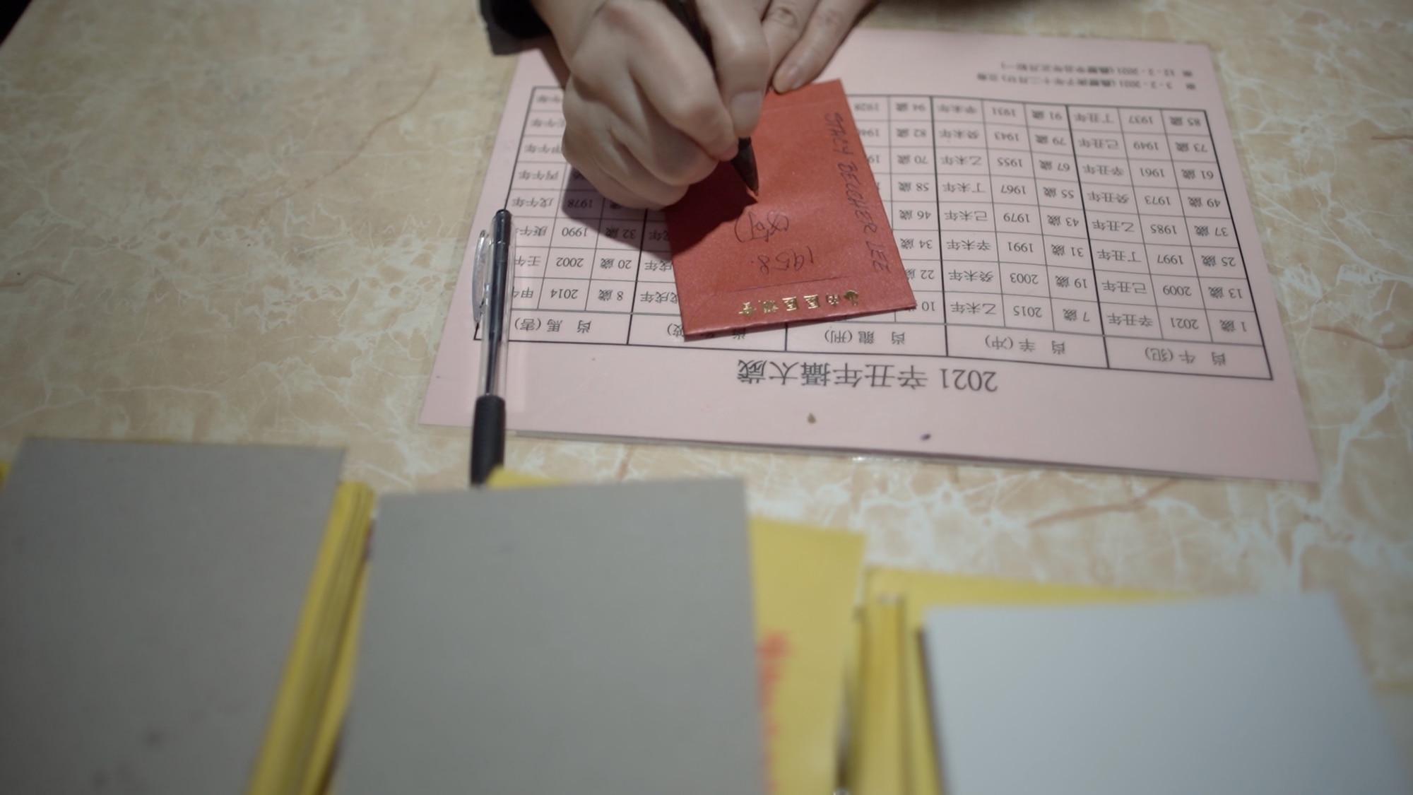 Stacy écrit son année de naissance et son signe du zodiaque sur le paquet rouge.