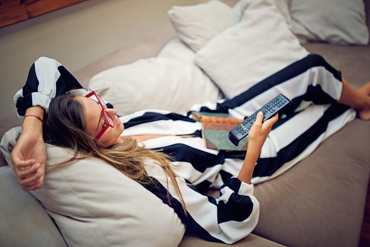 La jeune femme est allongée sur le canapé et regarde la télévision