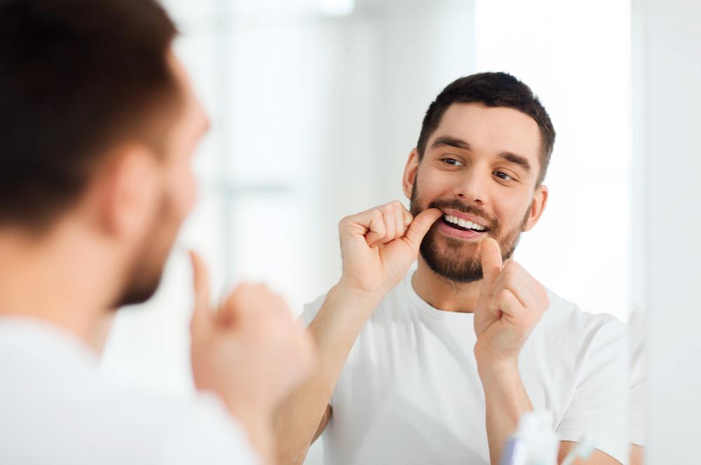 l'homme passe du fil dentaire en regardant dans un miroir