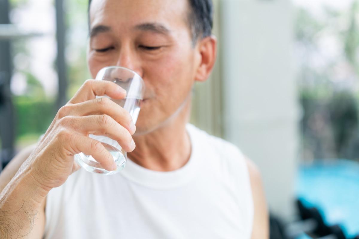 Un homme âgé boit de l'eau minérale dans le centre de remise en forme de la salle de sport après l'exercice. Mode de vie sain des personnes âgées.