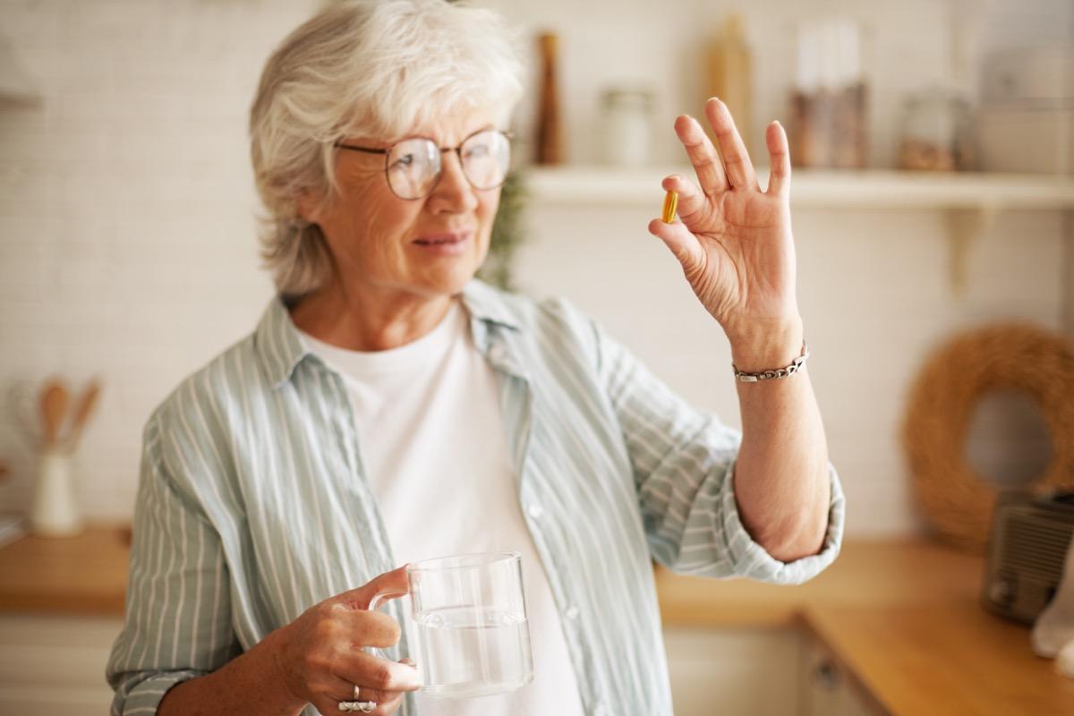 Femme prenant une pilule ou un supplément