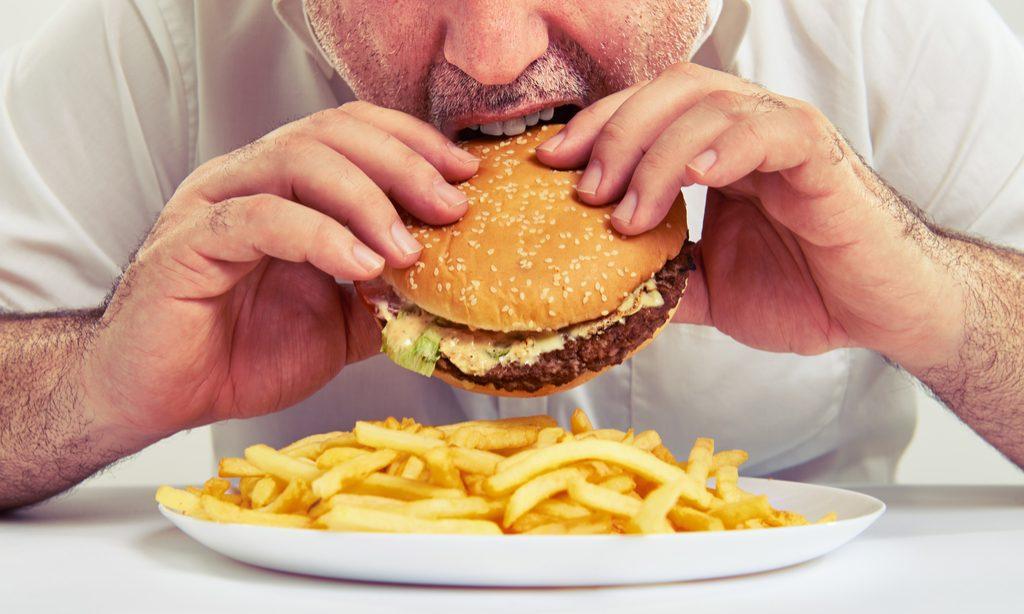 Man Eating Cheeseburger habitudes qui augmentent votre risque de cancer