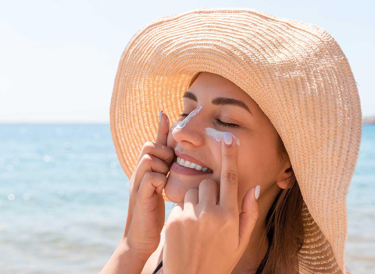 femme mettant de la crème solaire à la plage