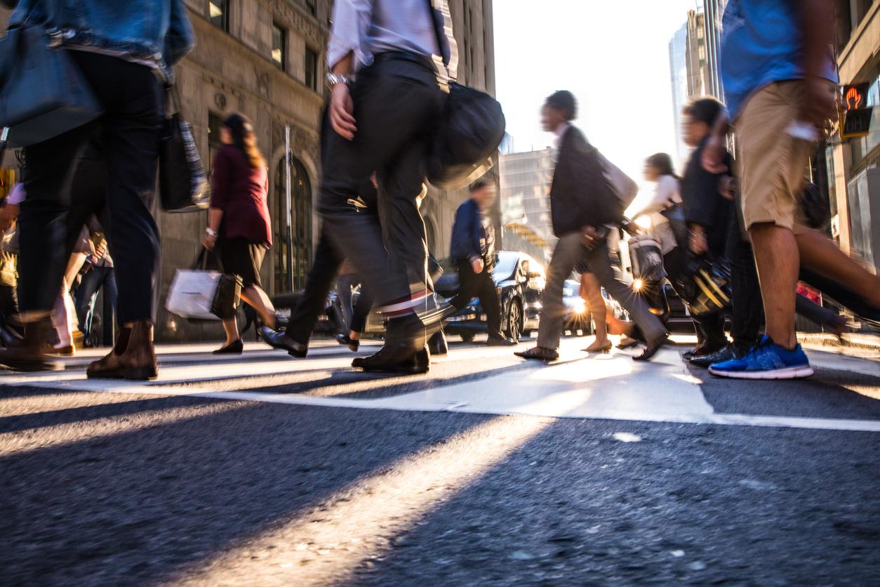 Les piétons traversent un passage pour piétons très fréquenté dans le centre-ville d'une ville.