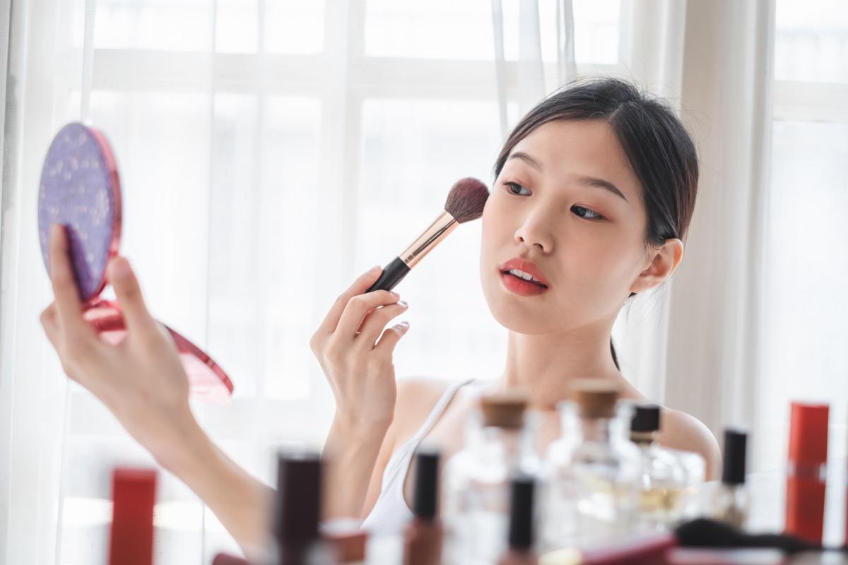 Jeune belle femme appliquant des cosmétiques sur son visage, soins de la peau beauté santé et concept de maquillage