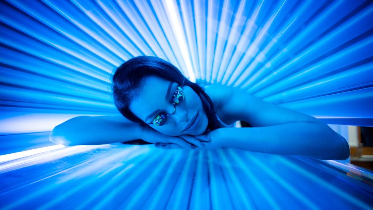 Jolie jeune femme bronzant au solarium et souriante.